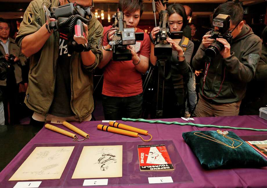 "Bruce Lee's most iconic martial arts weapons, including a pair of yellow lacquered wooden nunchaku, second from left, are displayed during an auction preview in Hong Kong, Monday, Dec. 2, 2013. It's part of a collection of 14 items including clothing and props going on the block on Thursday. Spink auction house estimates props from his movie ""Game of Death"" to be sold include the nunchaku expected to fetch $26,000-$38,700. (AP Photo/Vincent Yu) ORG XMIT: XVY102 Photo: Vincent Yu / AP"