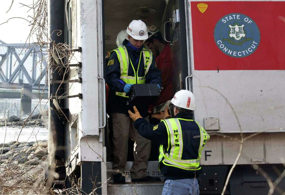 In a handout photo, National Transportation Safety Board investigators remove an event recorder from a Metro-North Railroad passenger train that derailed in the Bronx borough of New York, Dec. 1, 2013.  As investigators continued to search for clues as to why the train flew off the tracks on Sunday morning, killing four people and injuring dozens more, Gov. Andrew Cuomo said on Monday morning that it appeared that the train was traveling too fast as it hit a curve in the tracks. Photo: NTSB, National Transportation Safety B / National Transportation Safety Board via The New York Times via Associated Press