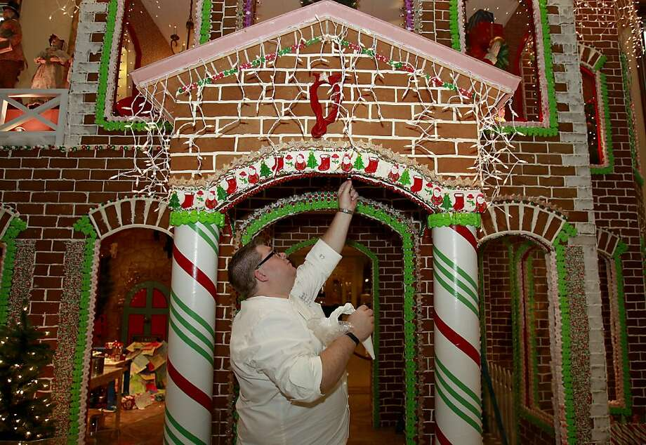 Fairmont Executive Chef Chad Blunston makes a little repair on his gingerbread house Thursday November 27, 2013 in San Francisco, Calif. The Fairmont Hotel on Nob Hill is finishing up it's famous gingerbread house which takes up a prominent place in the lobby along with other Christmas scenes. Photo: Brant Ward, The Chronicle