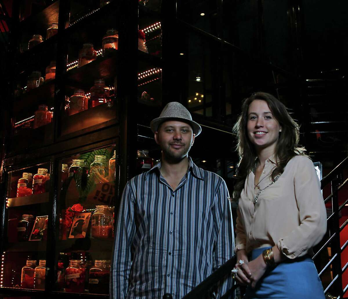 El Big Bad owners Steve Sharma and Lea McKinney stand in front of one of the restaurant's oddities - a cabinet of tequilas steeped in fruit and botanicals.