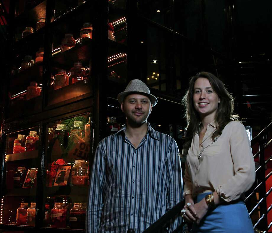 El Big Bad owners Steve Sharma and Lea McKinney stand in front of one of the restaurant's oddities - a cabinet of tequilas steeped in fruit and botanicals. Photo: James Nielsen, Staff / © 2013  Houston Chronicle