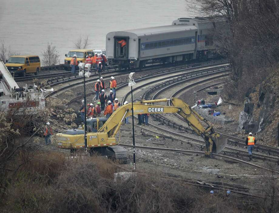 A construction machine moves a section of railroad track near the site of a deadly train derailment in the Bronx section of New York on Monday.