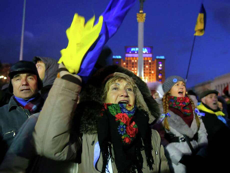 Protesters shout during a rally at the central Independence Square in Kiev, Ukraine, Monday, Dec. 2, 2013. Thousands of Ukrainian protesters on Monday besieged government buildings in Kiev and called for the ouster of the prime minister and his Cabinet, as anger at the president's decision to ditch a deal for closer ties with the European Union gripped other parts of the country and threatened his rule. (AP Photo/Sergei Grits) Photo: Sergei Grits, STF / AP
