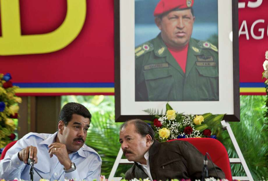 FILE - In this June 29, 2013 file photo, under a portrait of the late Hugo Chavez, Venezuela's President Nicolas Maduro, left, talks with Nicaragua's President Daniel Ortega during the 8th Petrocaribe Summit in Managua, Nicaragua. Chavez's dream of leveraging Venezuela's oil wealth to spread revolution across Latin America is crumbling under the weight of an economic crisis that has forced his hand-picked successor to cut back on generous foreign aid. (AP Photo/Esteban Felix, File) Photo: Esteban Felix, STF / AP
