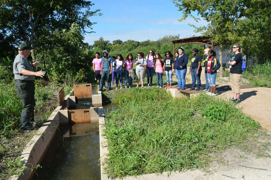 National Park Ranger Tom Castanos, left, explains to East Central High School students the workings of the acequia at the San Juan Demonstration Farm. By opening and closing gates, water can be diverted into fields that need irrigating. Photo: Courtesy Photo