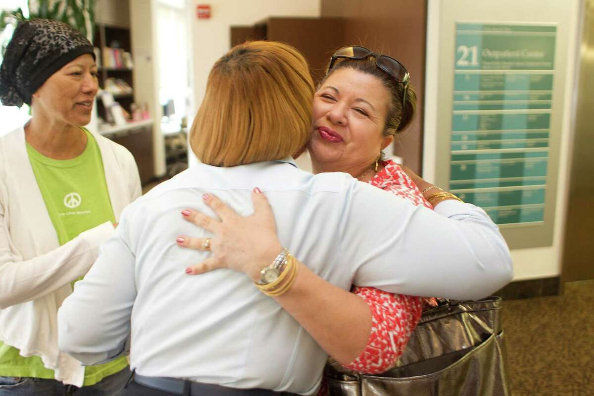 Ola Doureseau, 70, center, a patient navigator at Houston Methodist Cancer Center greets Paula Macias, right, and her sister-in-law, Cyndi Macias, left, who was receiving treatment Wednesday, Sept. 18, 2013, in Houston.