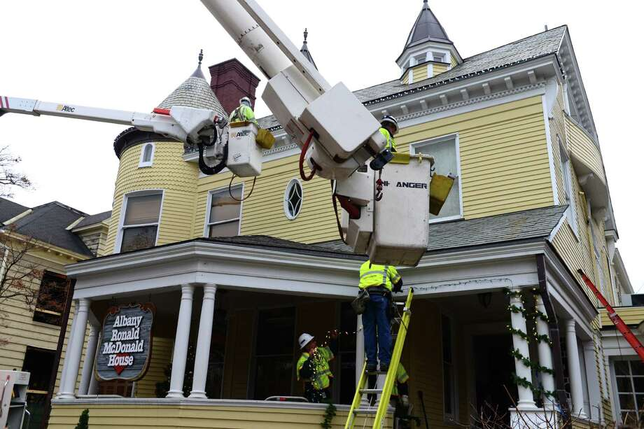 National Grid workers Tom Fox, upper left, and Don Lobdell, upper right, were part of a team who came out out to decorate Albany's Ronald McDonald House with LED lights and bunting Monday afternoon, Dec. 2, 2013, in Albany N.Y. National Grid crews strung LED lights around the entire front of the building. LED lights are said to consume 1/10 of the power used to illuminate conventional miniature bulbs. (Will Waldron/Times Union) Photo: WW / 00024853A