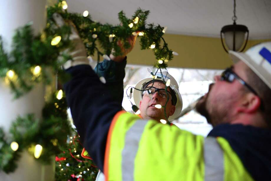 National Grid workers Larry Reisigl of Milton, left, Matthew Lee of Catskill, right, decorate Albany's Ronald McDonald House with LED lights and bunting Monday afternoon, Dec. 2, 2013, in Albany N.Y. National Grid crews strung LED lights around the entire front of the building. LED lights are said to consume 1/10 of the power used to illuminate conventional miniature bulbs. (Will Waldron/Times Union) Photo: WW / 00024853A