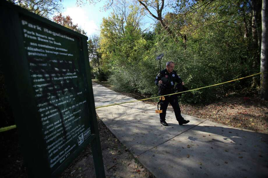 A police investigator leaves the trail where members of the MacArthur High School cross-country team and other joggers found the body of a male 17-year-old while running through Keith-Weiss Park. Photo: Mayra Beltran, Staff / © 2013 Houston Chronicle