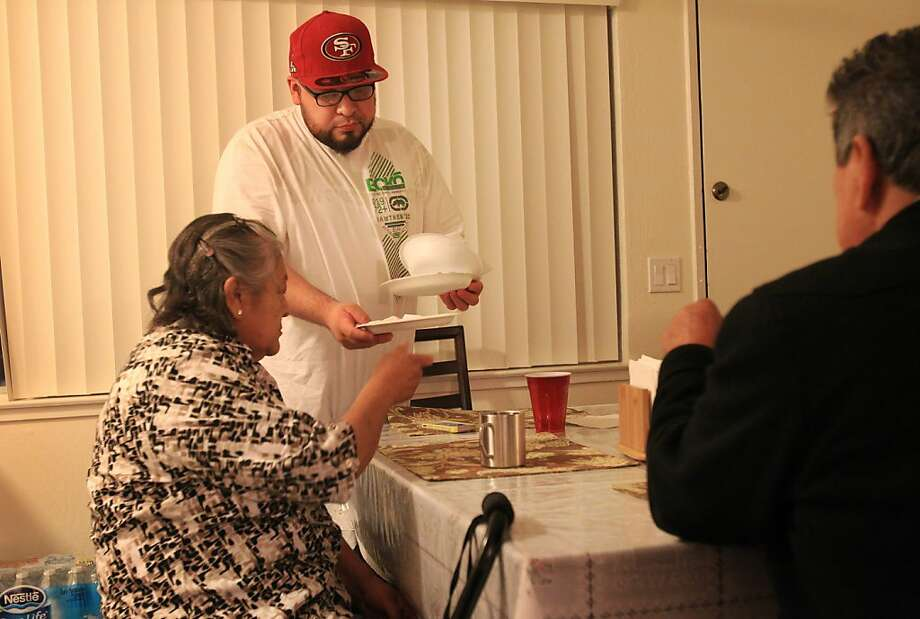 Humberto Campos (center) collects dishes from his parents, Graciela Sanchez and Raul Campos, in their Redwood City apartment. Photo: Leah Millis, The Chronicle