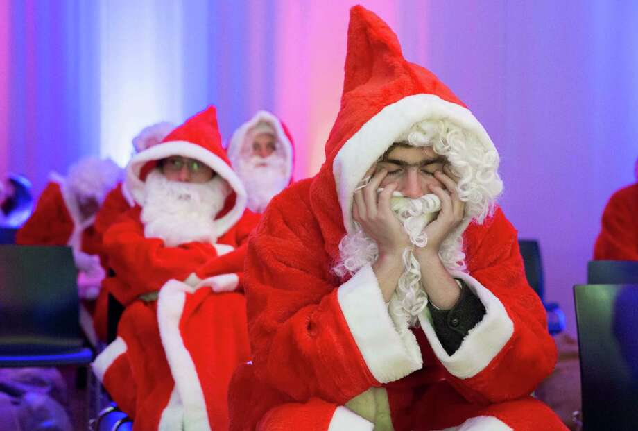 A man dressed as Santa Claus waits with his eyes closed for the beginning of the general meeting of Berlin's Santa Clauses and angels in Berlin, Germany, Saturday, Nov. 30, 2013. Students and others  are introduced at the meeting  how to  handle  their jobs in the German capital during this year's Christmas season. Photo: Gero Breloer, Associated Press / AP