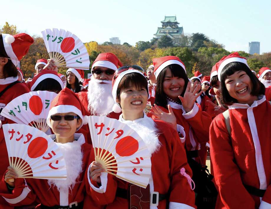 Participants dressed as Santa Claus get ready to jog before the 5th annual Osaka Great Santas run at fornt of the Osaka Castle on December 1, 2013 in Osaka, Japan. Participation fees will be donated to children who have to spend Christmas day in a hospital. Photo: Buddhika Weerasinghe, Getty Images / 2013 Getty Images