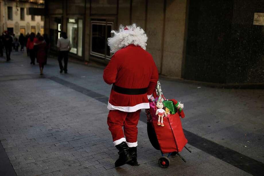 A man dressed as Santa Claus walks around the streets charging for photographs taken with him, in the centre of Madrid, Spain, Sunday, Dec. 1, 2013. With unemployment at 26 percent, the government admits that while the recession may have technically ended it could take years for the country to recover from the economic crisis, which began with a real estate collapse in 2008. Photo: Andres Kudacki, Associated Press / AP