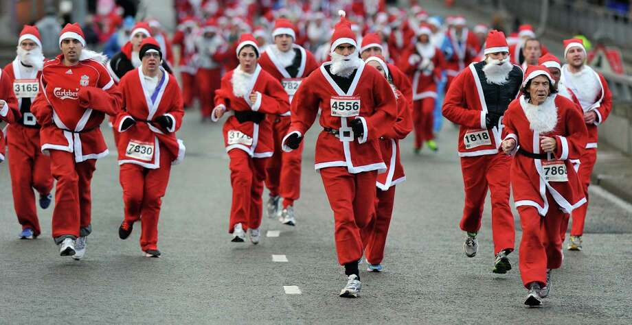 Runners dressed in Father Christmas costumes take part in the annual five kilometer Santa Dash in Liverpool, north-west England, on December 1, 2013. Organizers were hoping to attract as many as 10,000 runners to this year's race. Many runners wear a blue suit, usually supporters of Everton FC, who refuse to run in red and white, the colours of their city rivals Liverpool FC. Photo: PAUL ELLIS, AFP/Getty Images / AFP
