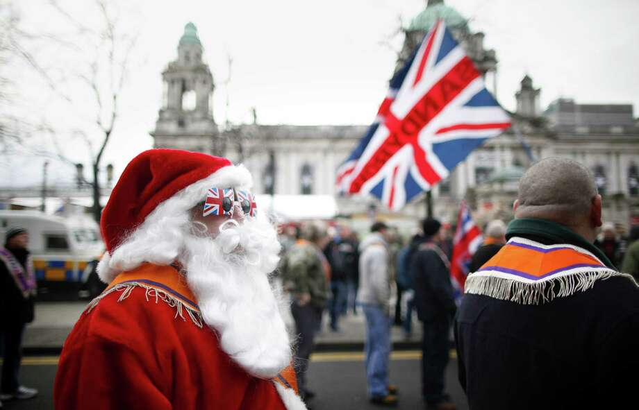 A Orangeman dressed as Santa takes part in the Loyalist flag protest at Belfast City Hall, Northern Ireland, Saturday, Nov. 30, 2013. Hundreds of people are taking part in a loyalist protest march which gathered at Belfast City Hall. The protesters have breached a determination by the Parades Commission that they leave the city hall by noon. The march comes days ahead of the first anniversary of the council's decision to restrict the flying of the union flag to designated days. Photo: Peter Morrison, Associated Press / AP