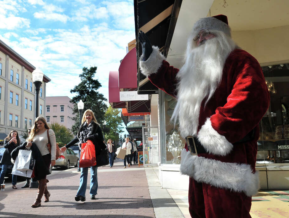Santa waves to shoppers as they pass 24e  Design Co.while Black Friday shopping Friday, Nov. 29, 2013 on Broughton Street in Savannah, Ga. Photo: Richard Burkhart, Associated Press / Savannah Morning News