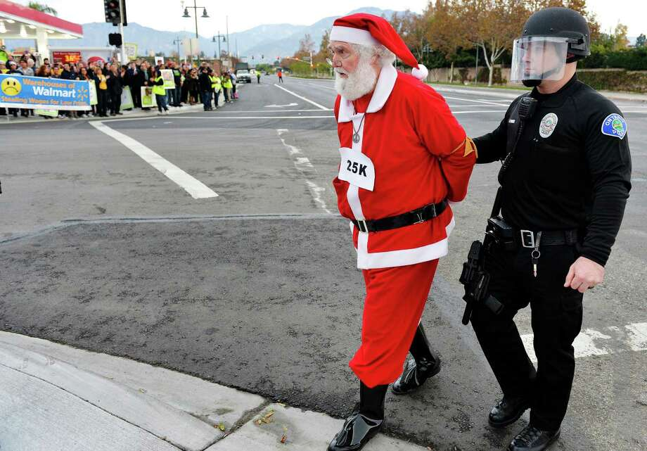 Wal-Mart protester Karl Hilgert, dressed as Santa Claus, is led away after being arrested for failure to disperse after sitting down with nine other protesters in the middle of an intersection on Friday, Nov. 29, 2013, in Ontario, Calif. A labor group and supporters used the Black Friday shopping period for a demonstration over wages and working conditions at Wal-Mart. Photo: Will Lester, Associated Press / The Inland Valley Daily Bulletin