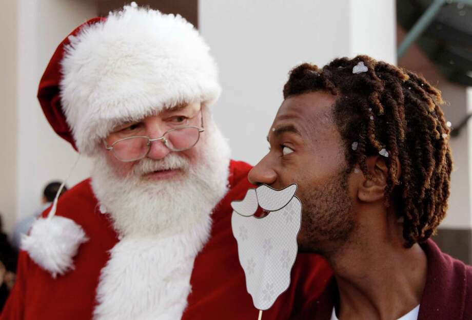 Santa gives Palais Royal store manager RaShaun Dickens a look as he imitates him in line at the Meyerland shopping center on Thursday, Nov. 28, 2013, in Houston. Photo: J. Patric Schneider, Associated Press / Houston Chronicle