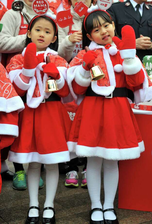 South Korean children wearing Santa Claus outfits hold bells during a ceremony to prepare charity pots for a year-end fund-raising campaign at Seoul Plaza in Seoul on November 27, 2013. The Salvation Army will launch its year-end charity campaign for poor people from December 2. Photo: JUNG YEON-JE, AFP/Getty Images / AFP