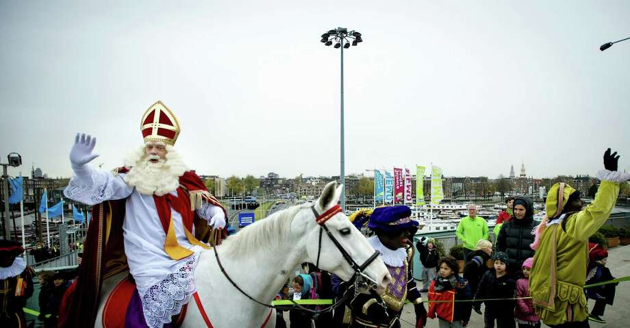 A man dressed as Saint Nicholas rides his horse Amerigo on the roof of the NEMO technology Museum in Amsterdam, on November 20, 2013, a few days before the celebration of the birthday of the saint on december 5. Photo: ROBIN VAN LONKHUIJSEN, AFP/Getty Images / AFP