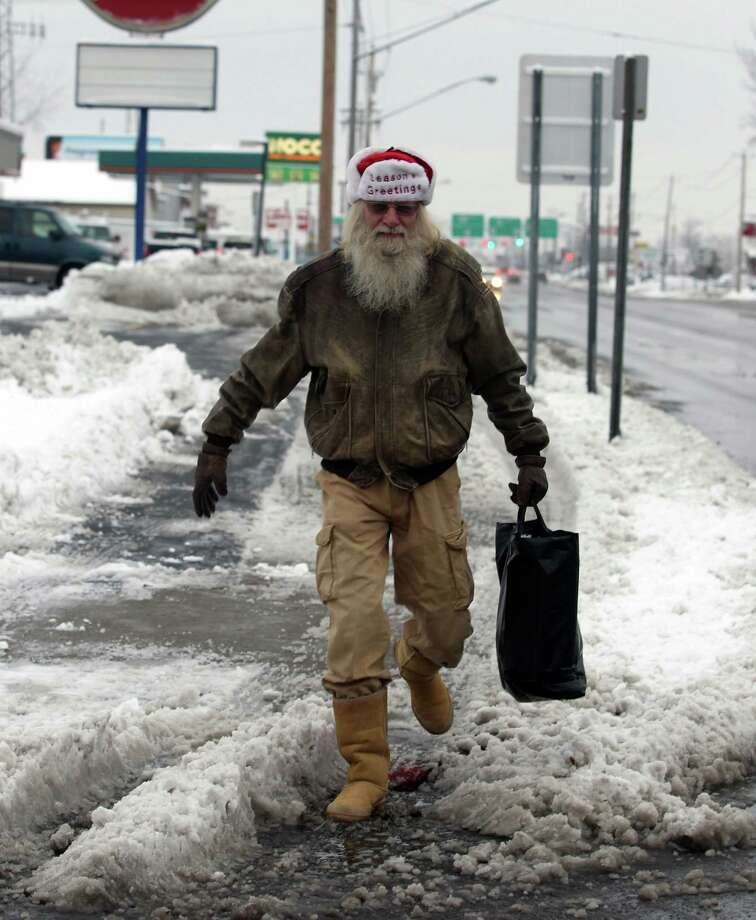 Florian Rzepka heads off to work as Santa Claus on Niagara Falls Blvd. in Tonawanda , N.Y. on Wednesday, Nov. 27, 2013. An overnight snowfall blanketed the area. Photo: John Hickey, Associated Press / The Buffalo News