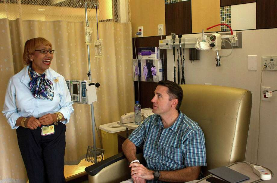 """Ola Doureseau, 70, a patient navigator at Houston Methodist Cancer Center, checks on patient Jud Bailey as he was receiving a cancer treatment in mid-September. """"She makes a bad situation a little bit better,"""" Bailey said. Photo: Johnny Hanson, Staff / Houston Chronicle"""