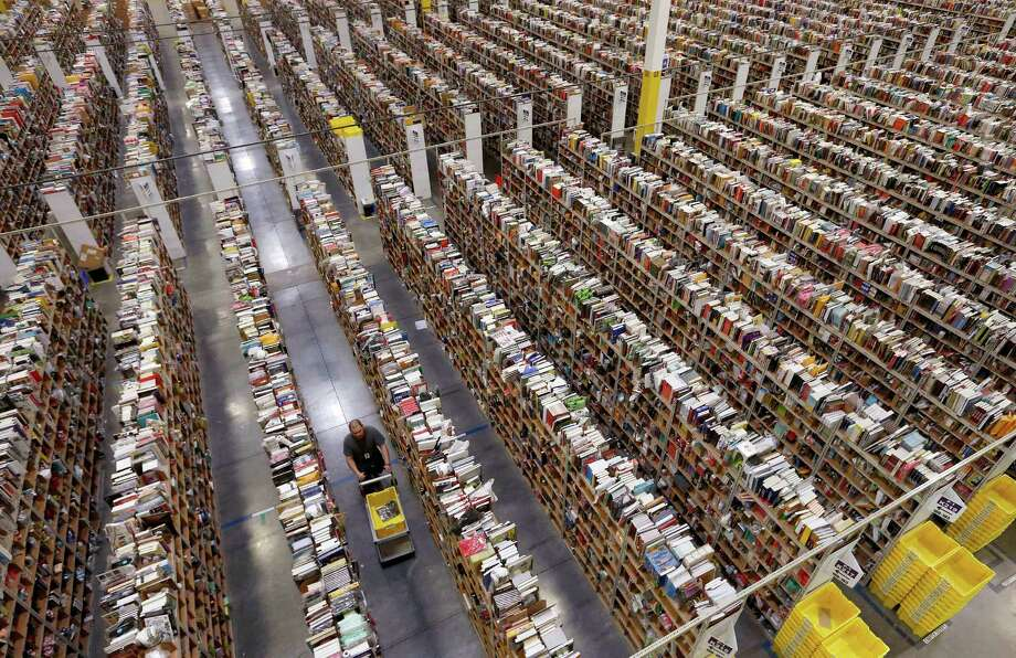 An employee walks down one of the miles of isles at an Amazon.com fulfillment center in Phoenix on Cyber Monday, the busiest online shopping day of the holiday season.  More than 131 million people were expected to shop during Cyber Monday events. Photo: Ross D. Franklin, STF / AP