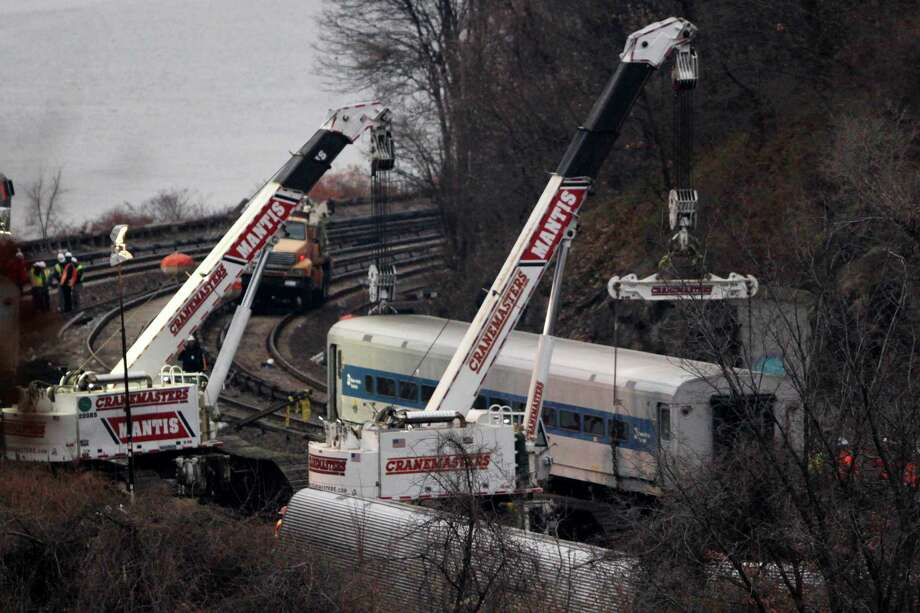 "Cranes lift a derailed Metro-North train car, Monday, Dec. 2, 2013, in the Bronx borough of New York. Federal authorities began righting the cars Monday morning as they started an exhaustive investigation into what caused a New York City commuter train rounding a riverside curve to derail, killing four people and injuring more than 60 others. A second ""event recorder"" retrieved from the train may provide information on the speed of the train, how the brakes were applied, and the throttle setting, a member of the National Transportation Safety Board said Monday.  (AP Photo/Mark Lennihan) ORG XMIT: NYML101 Photo: Mark Lennihan / AP"