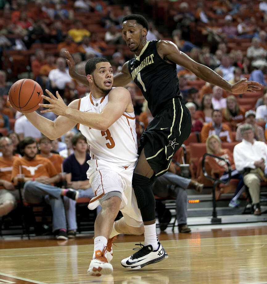 Texas's Javan Felix, left, passes around Vanderbilt's Eric McClellan during the first half of an NCAA college basketball game in Austin, Texas, on Monday, Dec. 2, 2013. (AP Photo/Austin American-Statesman, Deborah Cannon) Photo: Deborah Cannon, Associated Press / Austin American-Statesman