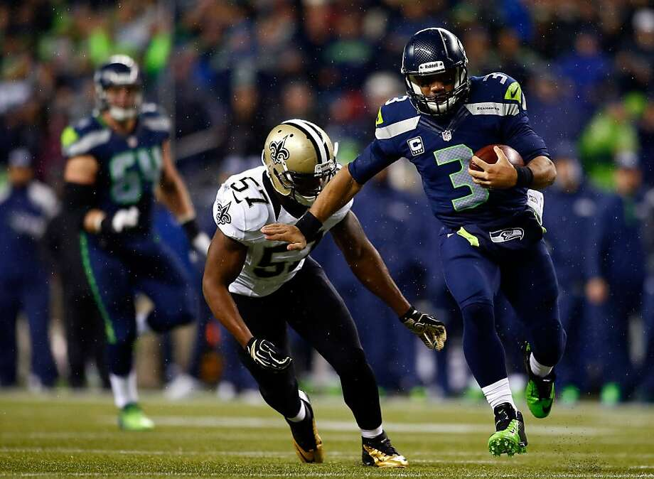 Quarterback Russell Wilson races past the Saints' David Hawthorne in, fittingly, a runaway victory for the Seahawks. Photo: Jonathan Ferrey, Getty Images