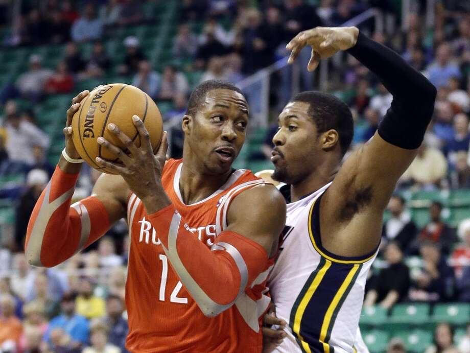 Rockets center Dwight Howard tries to make a move against Derrick Favors of the Jazz. Photo: Rick Bowmer, Associated Press