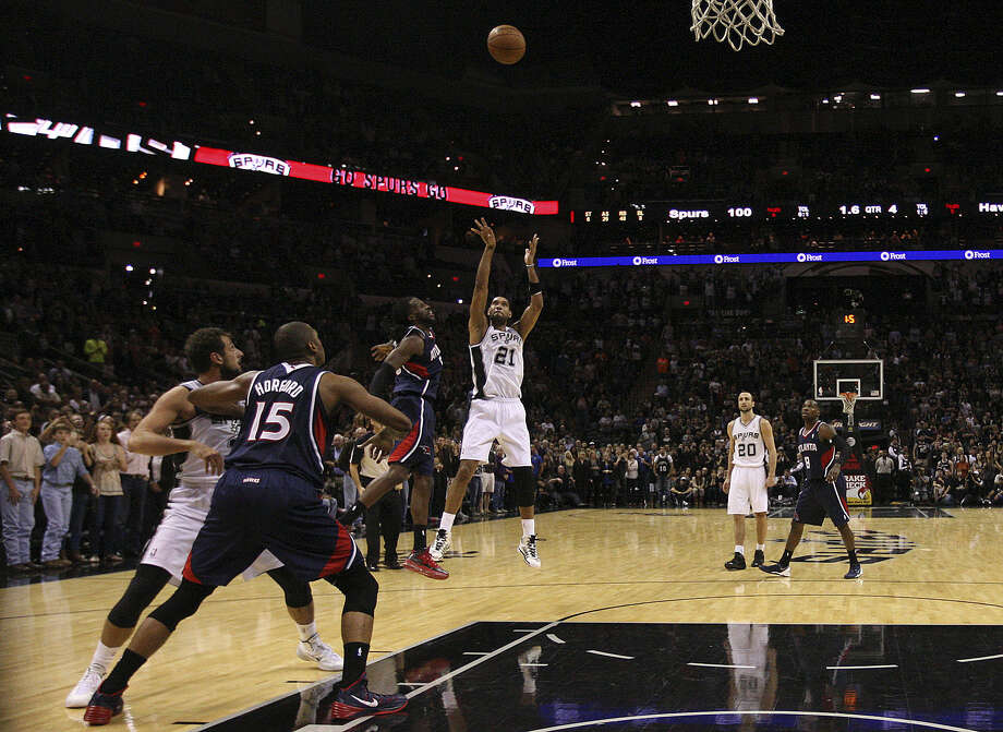 Spurs forward Tim Duncan fires up the game-winning shot with 0.4 seconds left against the Hawks despite the defensive efforts of DeMarre Carroll.