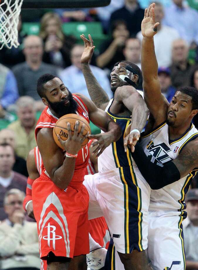 The Rockets' James Harden, left, pulls a rebound away from the Jazz's Marvin Williams, center, and Derrick Favors in the first quarter of Monday night's game, in which Harden scored 37 points. Photo: Rick Bowmer, STF / AP