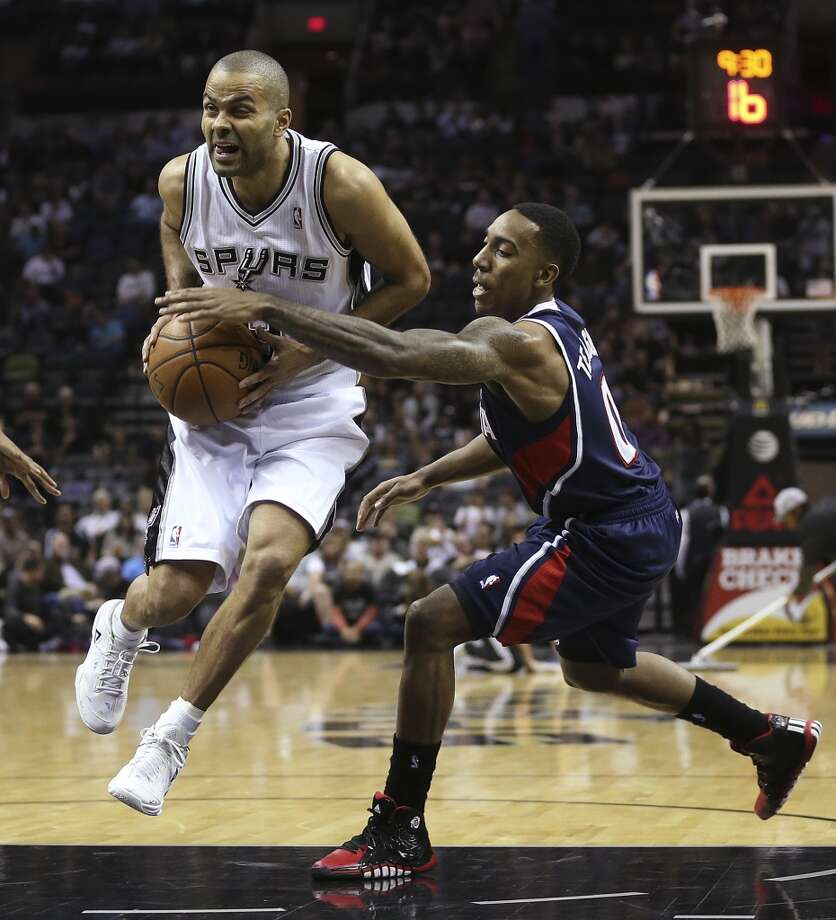 San Antonio Spurs' Tony Parker drives by Atlanta Hawks' Jeff Teague during the first half at the AT&T Center, Monday, Dec. 2, 2013. Photo: Jerry Lara, San Antonio Express-News