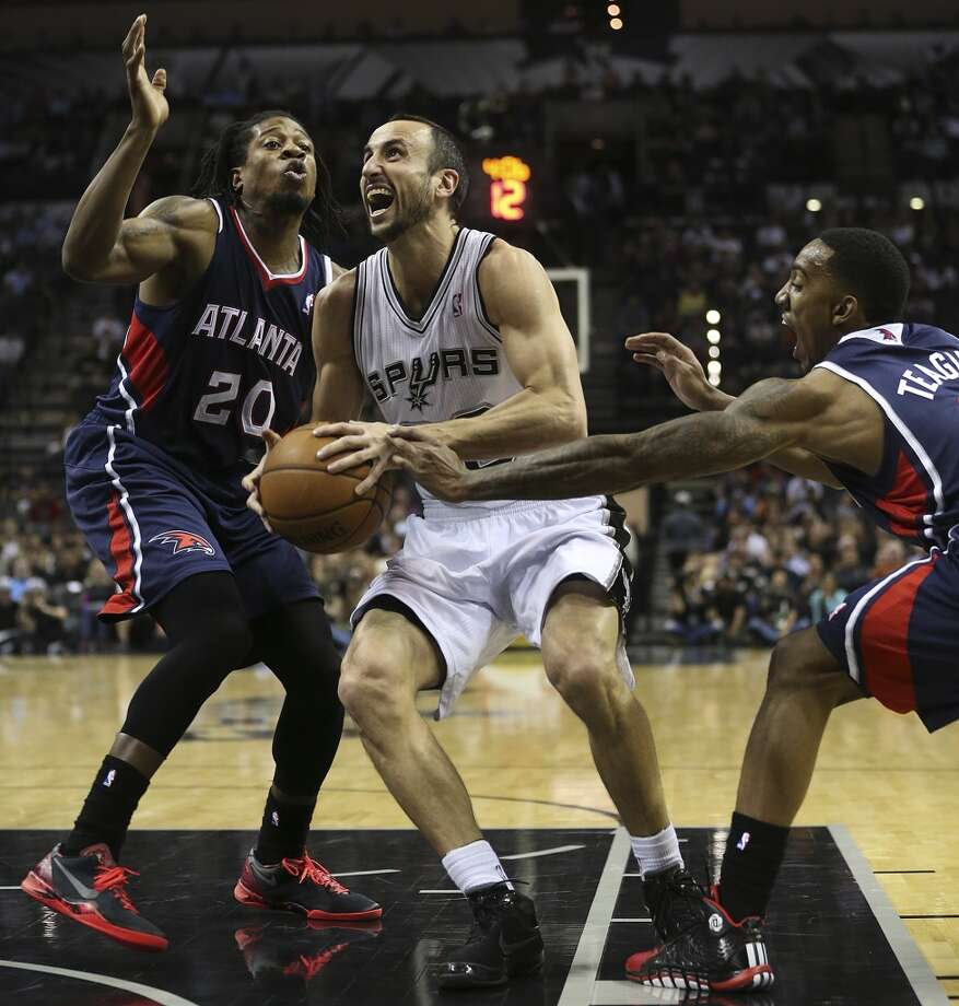 San Antonio Spurs' Manu Ginobili splits the defense of Atlanta Hawks' Cartier Martin, left, and Jeff Teague during the first half at the AT&T Center, Monday, Dec. 2, 2013. Photo: Jerry Lara, San Antonio Express-News