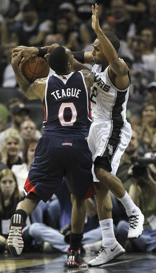 San Antonio Spurs' Patty Mills ties up Atlanta Hawks' Jeff Teague during the first half at the AT&T Center, Monday, Dec. 2, 2013. Photo: Jerry Lara, San Antonio Express-News