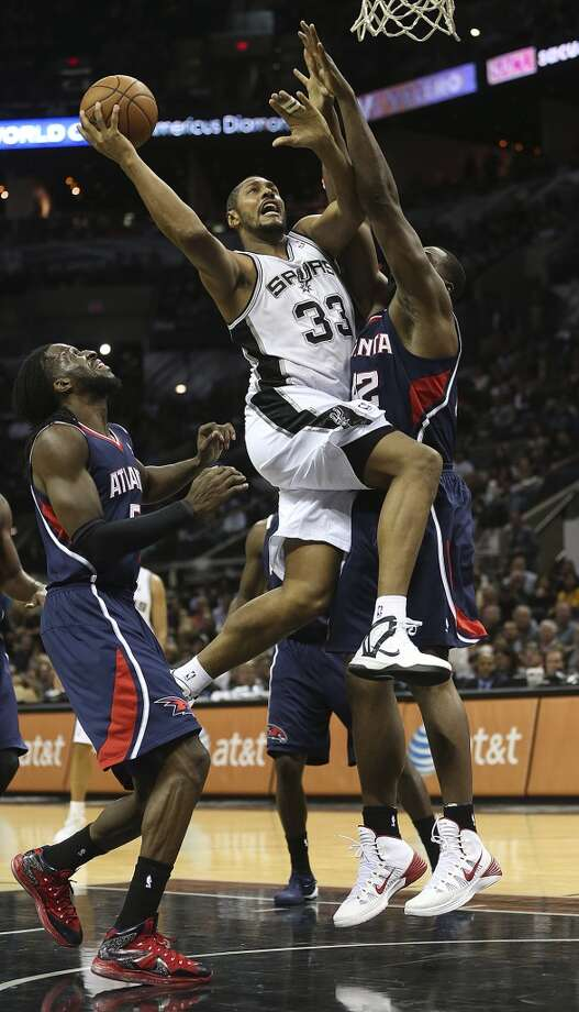 San Antonio Spurs' Boris Diaw drives through Atlanta Hawks' DeMarre Carroll, left, and Elton Brand during the second half at the AT&T Center, Monday, Dec. 2, 2013. The Spurs won 102-100. Photo: Jerry Lara, San Antonio Express-News