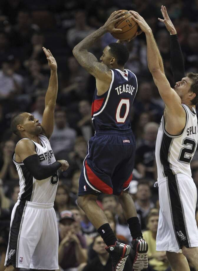 San Antonio Spurs' Patty Mills, left, and Tiago Splitter put pressure on Atlanta Hawks' Jeff Teague during the second half at the AT&T Center, Monday, Dec. 2, 2013. The Spurs won 102-100. Photo: Jerry Lara, San Antonio Express-News