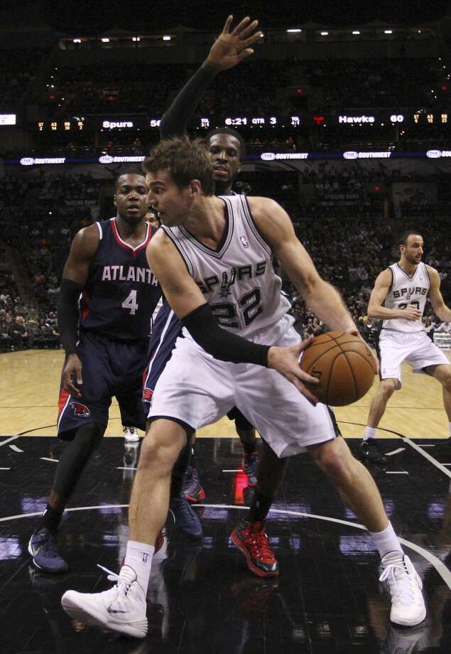 San Antonio Spurs' Tiago Splitter looks to pass to the perimeter as Atlanta Hawks' Paul Millsap, (4), and DeMarre Carroll defend during the second half at the AT&T Center, Monday, Dec. 2, 2013. The Spurs won 102-100. Photo: Jerry Lara, San Antonio Express-News