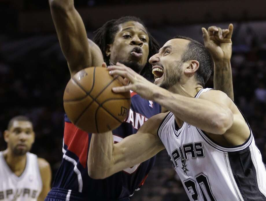 San Antonio Spurs' Manu Ginobili,right, of Argentina, is defended by Atlanta Hawks' Cartier Martin, left, as he drives to score during the first half of an NBA basketball game, Monday,  Dec. 2, 2013, in San Antonio. Photo: Eric Gay, Associated Press