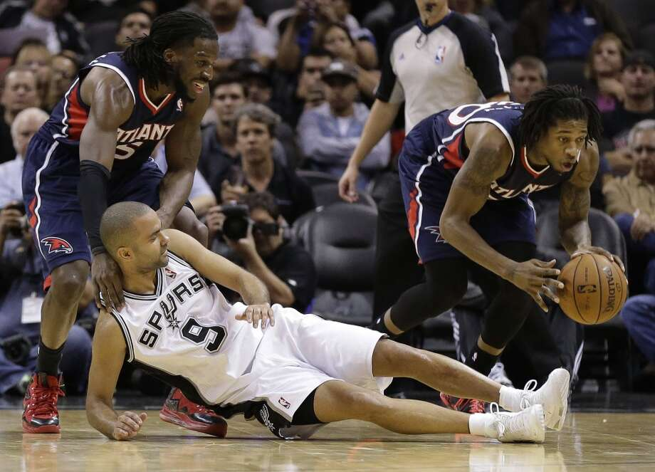Atlanta Hawks' Cartier Martin, right, steals the ball as San Antonio Spurs' Tony Parker (9), of France, fall to the floor during the second half of an NBA basketball game, Monday,  Dec. 2, 2013, in San Antonio. Atlanta Hawks' DeMarre Carroll, left, assists on the play. Photo: Eric Gay, Associated Press