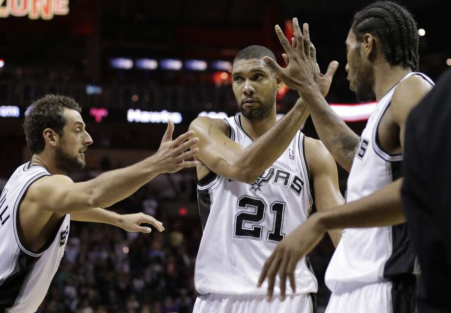 San Antonio Spurs' Tim Duncan (21) celebrates with teammates Marco Belinelli, left, and Kawhi Leonard, right, following an NBA basketball game against the Atlanta Hawks, Monday,  Dec. 2, 2013, in San Antonio. Duncan scored with less that one second remaining in the game. San Antonio won 102-100. Photo: Eric Gay, Associated Press
