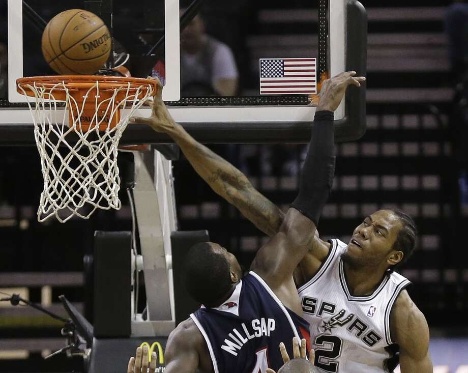 San Antonio Spurs' Kawhi Leonard (2) goes to the basket over Atlanta Hawks' Paul Millsap (4) during the second half of an NBA basketball game, Monday,  Dec. 2, 2013, in San Antonio. San Antonio won 102-100. Photo: Eric Gay, Associated Press