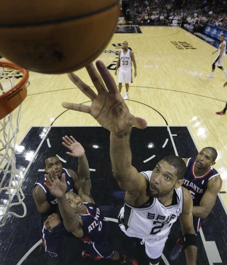 San Antonio Spurs' Tim Duncan (21) scores over Atlanta Hawks' Paul Millsap, left, Jeff Teague (0) and Al Horford, right, during the second half of an NBA basketball game, Monday,  Dec. 2, 2013, in San Antonio. San Antonio won 102-100. Photo: Eric Gay, Associated Press