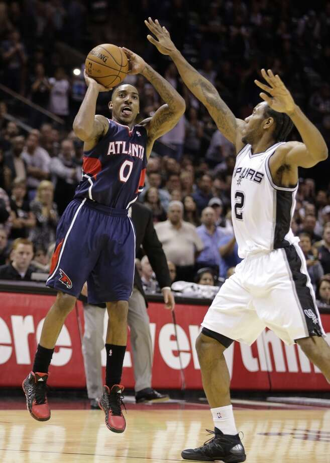 Atlanta Hawks' Jeff Teague (0) shoots a three-point  shot over San Antonio Spurs' Kawhi Leonard (2) during the second half of an NBA basketball game, Monday,  Dec. 2, 2013, in San Antonio. San Antonio won 102-100. Photo: Eric Gay, Associated Press