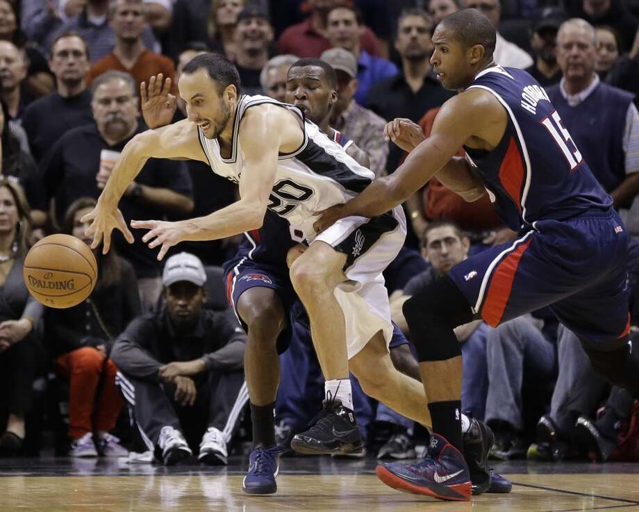 San Antonio Spurs' Manu Ginobili (20), of Argentina (20) is pressured by Atlanta Hawks' Al Horford (15) and Shelvin Mack, center, during the second half of an NBA basketball game, Monday,  Dec. 2, 2013, in San Antonio. San Antonio won 102-100. Photo: Eric Gay, Associated Press