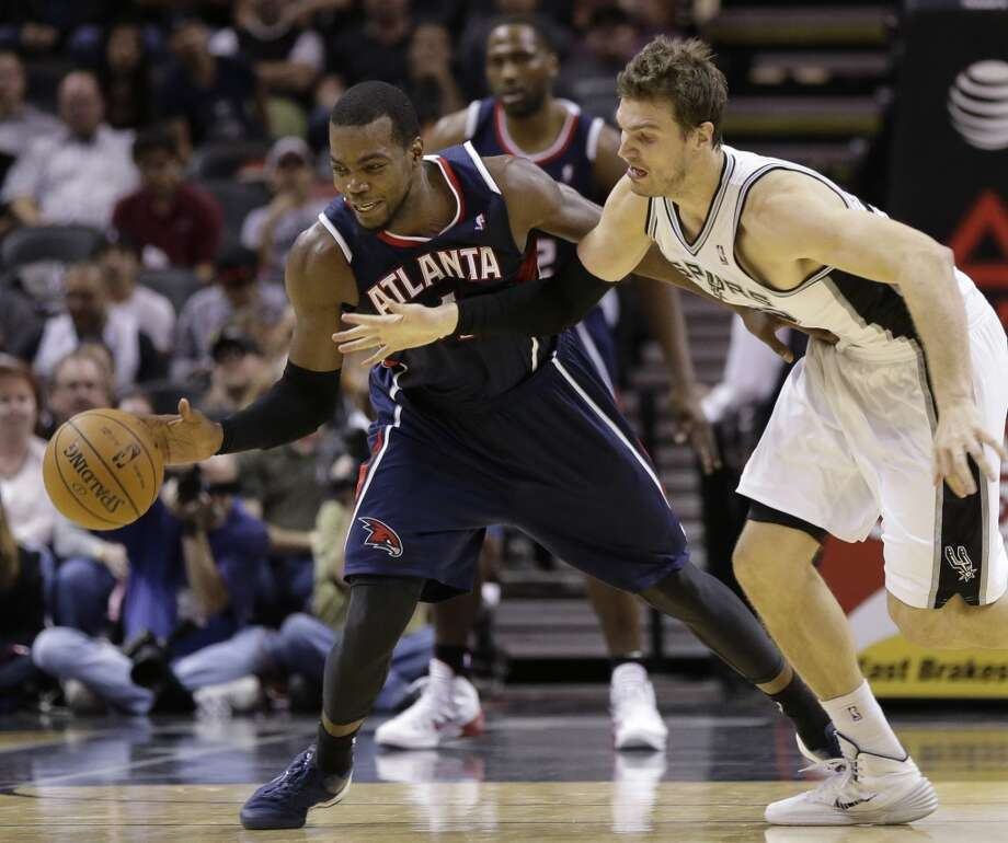 Atlanta Hawks' Paul Millsap, left, steals the ball from San Antonio Spurs' Tiago Splitter, right, of Brazil, during the second half of an NBA basketball game, Monday,  Dec. 2, 2013, in San Antonio. Photo: Eric Gay, Associated Press