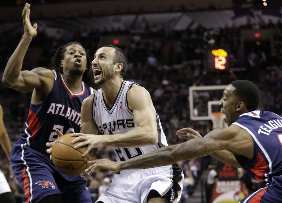 San Antonio Spurs' Manu Ginobili, center,  of Argentina, is pressured by Atlanta Hawks' Cartier Martin, left, and Jeff Teague, right, as he drives to the basket during the first half of an NBA basketball game, Monday,  Dec. 2, 2013, in San Antonio. Photo: Eric Gay, Associated Press