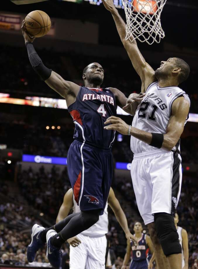 Atlanta Hawks' Paul Millsap (4) drives as San Antonio Spurs' Tim Duncan (21) during the second half of an NBA basketball game, Monday,  Dec. 2, 2013, in San Antonio. San Antonio won 102-100. Photo: Eric Gay, Associated Press
