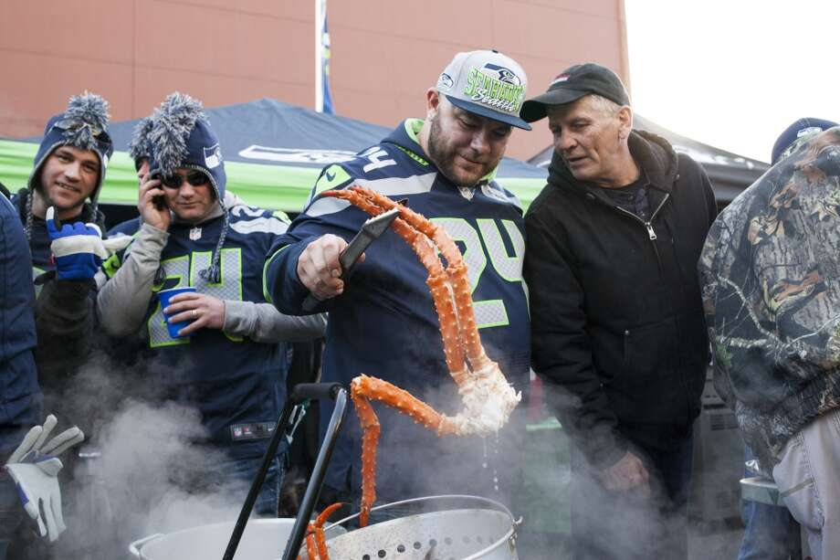 Dane Richardson pulls out a fresh king crab leg during tailgating festivities before the start of the Seahawks and Saints game Monday, Dec. 2, 2013, at CenturyLink Field in Seattle. Photo: MARK MALIJAN, SEATTLEPI.COM